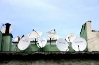 Mehrere Satellitenschüsseln auf einem Dach